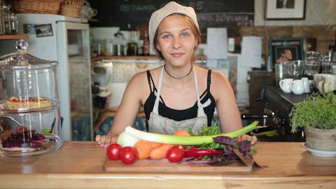 Female chef showing vegetables on cutting board Live Action