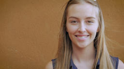 Hand held portrait of a beautiful blond teen women smiling with her long hair bl Footage