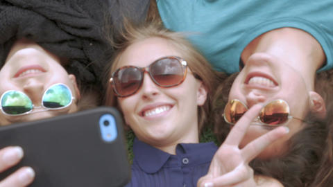 Three attractive female best friends take a selfie while lying next to each othe Footage