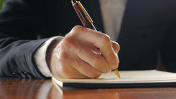 Closeup of business man writing in notebook with pen while sitting at a desk dur Live Action