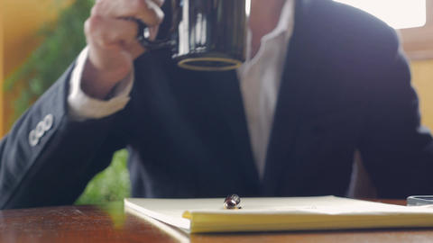 Closeup of business man hand writing in a yellow legal notebook while drinking h Footage