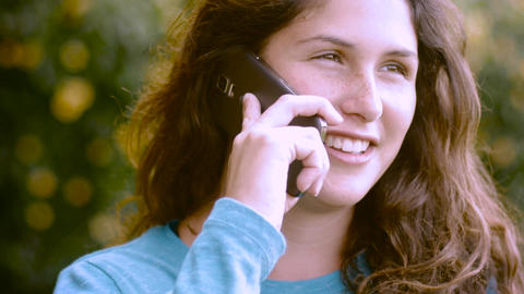 An attractive young woman with long brown hair answers her phone and smiles outs Footage