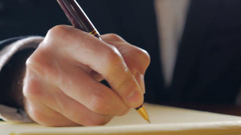 Closeup of business man hand writing in yellow legal pad with a ball point pen w Footage