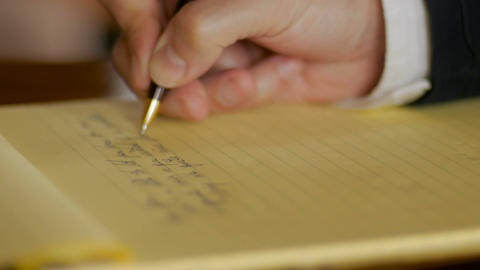 Businessman hand writing letter in legal pad yellow notebook with ball point pen Footage