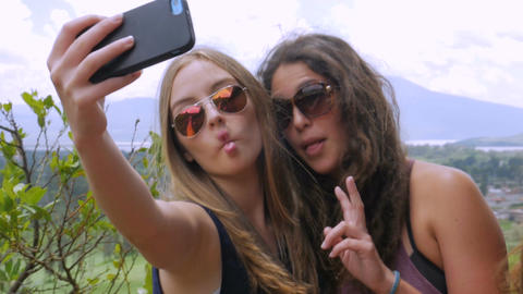 Young beautiful teenage girls make silly faces for a selfie in slow mo in the su Footage