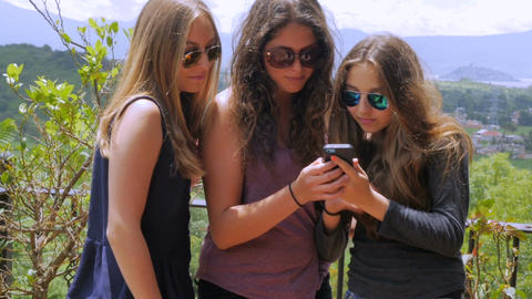 Three gorgeous teenage girls take multiple selfies and look at their cell phone  Footage