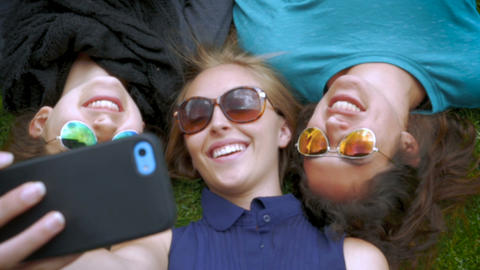 Three best friends take a selfie while lying next to each other in slow motion Footage