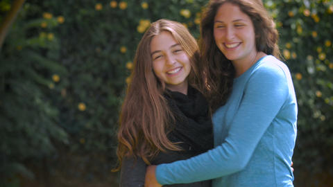 Two attractive teenage sisters hug, smile, and laugh for the camera in slow mo Footage