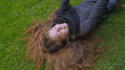 A young attractive teenage girl is lifted off the grass by her friends and then Footage