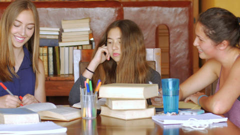 Three beautiful teenage girls learn together with books at a table in a modern l Footage