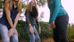 Low angle handheld of attractive teenage girls dancing in slow mo Footage