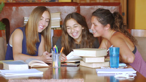 An attractive teen shares her phone with her friends while studying at a modern Footage