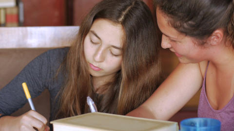 Push in of two teenager girls studying together and having a good time in their Footage