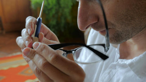 Close up of man repairing prescription glasses with tiny screwdriver - handheld Footage