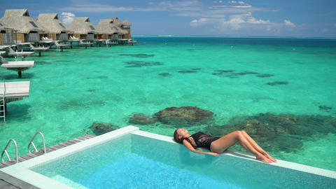 Luxury hotel Tahiti vacation swimsuit model woman relaxing sunbathing by pool Live Action