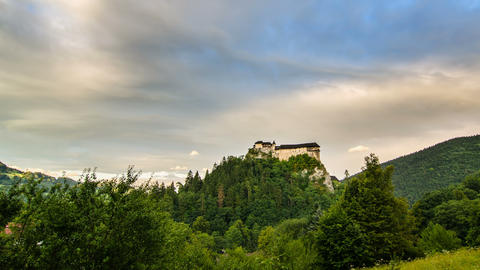 Clouds over historic castle in green forest country in evening Time lapse Footage