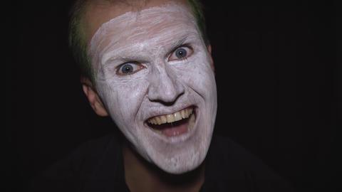 Clown Halloween man portrait. Close-up of an evil clowns face. White face makeup Footage