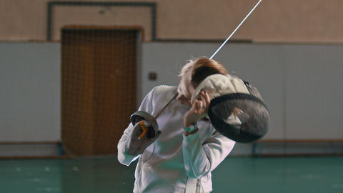 A young woman fencer with long blonde hair takes off a protective helmet holding Footage