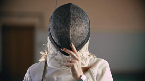 A young woman fencer takes off a protective helmet holding a sword Footage