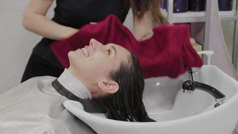 Hairdresser salon. A hairdresser is wiping his clients hair in the sink with a Live Action