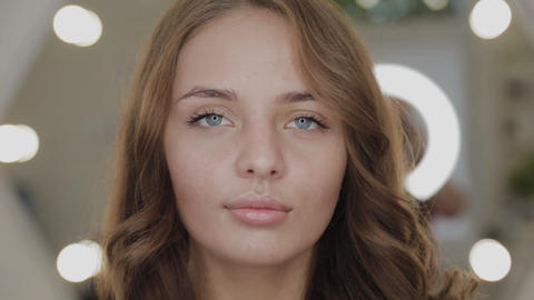 Beautiful girl in a beauty salon near the backlit mirror. Woman portrait Live Action