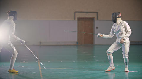 Two young women fencers in protective clothes having a training in the gym Footage