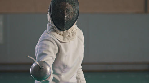 A young woman fencer in protective suit and helmet making lunges to the camera Footage