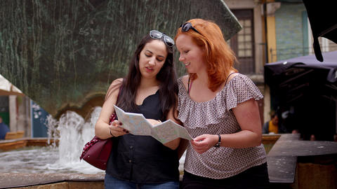 Two girls checking destinations on a map Live Action