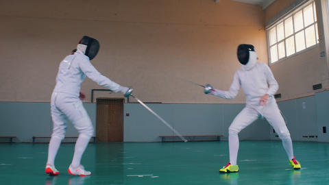 Two young women in white costumes having a fencing training in the school gym Live Action