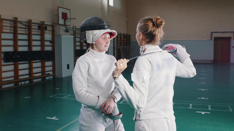 Two young women fencers in white protective suits standing on front of each Footage