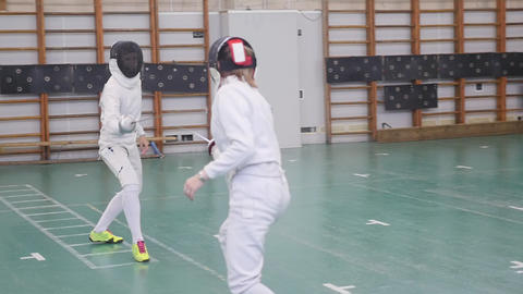 Two young women having an active fencing training in the school gym Footage
