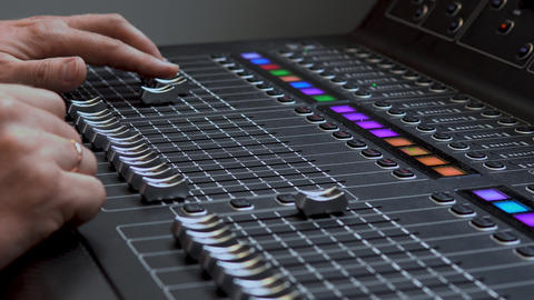 Man works on a professional electronic audio mixer. A control panel for tuning Live Action