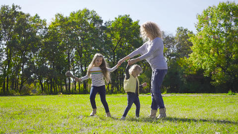 Blond caucasian woman with curly hair dancing with two pretty little girls on Footage
