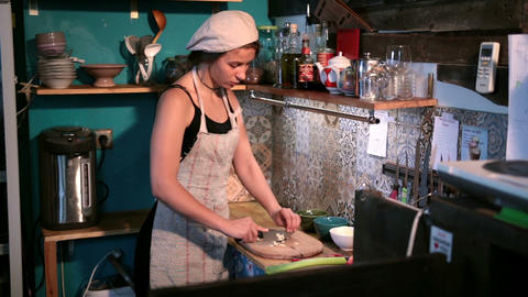 Charming woman chopping garlic on wooden board Footage