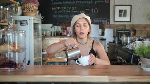 Cute female barista pouring milk into coffee cup Footage
