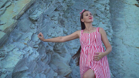 Young pregnant girl in a striped red and white dress. A girl stands at the foot Live Action