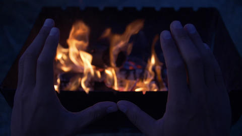 Slow motion hands of the man that is warm his hands near the bonfire at the Live Action