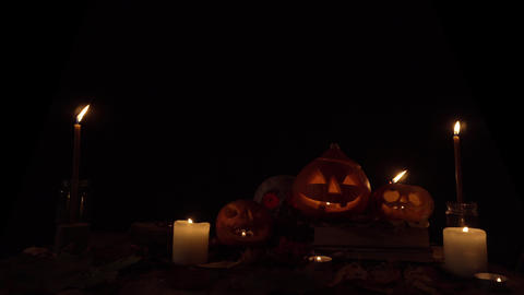 Pumpkins with carved faces and a skull in candlelight, loop video Live Action