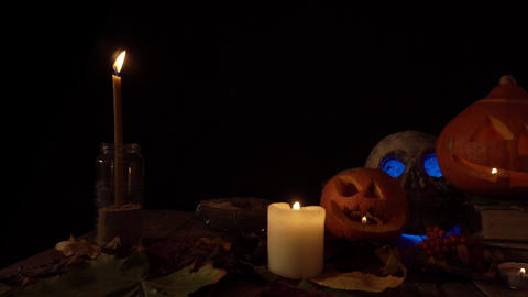 Halloween decorations two pumpkin lanterns and a human skull in candlelight Live Action