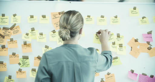 Female executive brainstorming with sticky notes Live Action