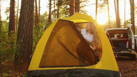 Tourist girl waking up inside camping tent in morning forest. Young girl Live Action