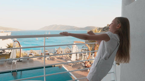 Happy teenager girl holding handrail and swaying on balcony resort hotel at Footage