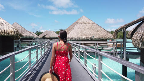 Vacation Travel woman walking on pontoon of overwater bungalow resort hotel Footage