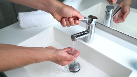 Man washing hands in bathroom sink at home checking temperature with hand Live Action