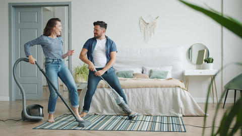 Girl and guy vacuuming carpet in bedroom laughing having fun during clean-up Live Action