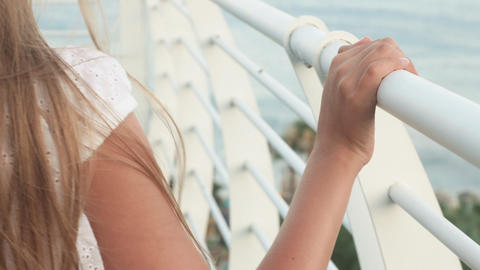 Female hand sliding on white handrail summer balcony with sea view. Close up Footage