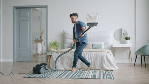 Attractive man vacuuming carpet with vacuum cleaner and having fun dancing Footage