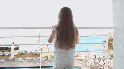 Tourist girl entering on balcony with sea view in resort hotel. Traveling girl Live Action