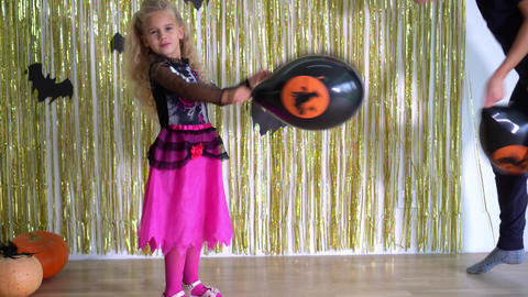 girl dressed in Halloween play with balloons. pumpkins and bats background. 4K GIF