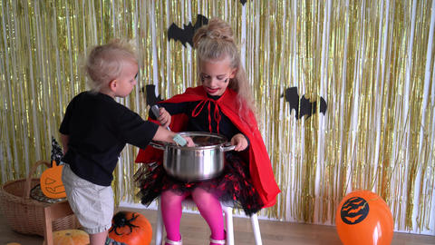 children mix sweets in large pot. Children play on Halloween holiday. 4K Footage